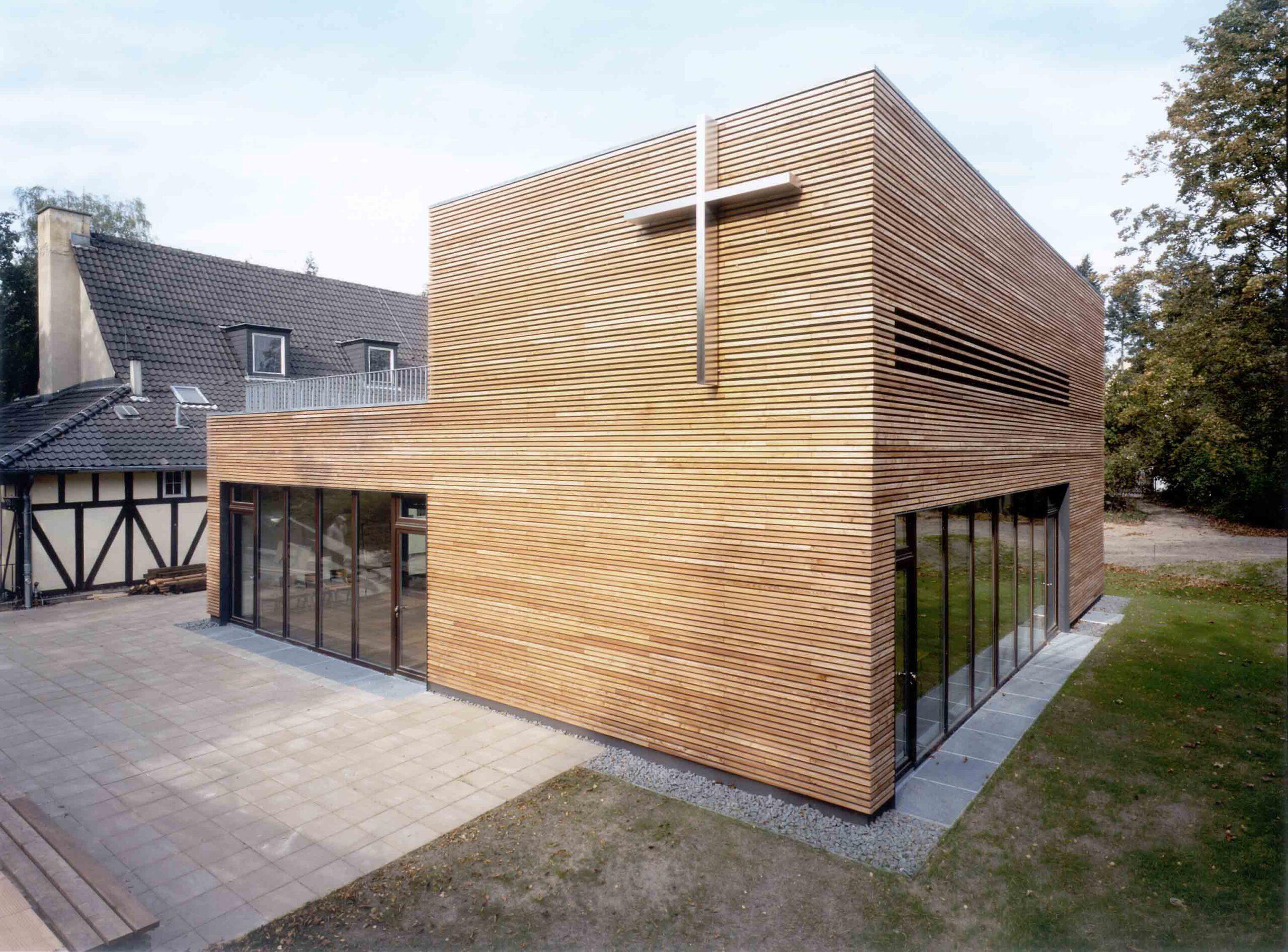 Erweiterungsbau mit denkmalgeschützter Kirche im Hintergrund